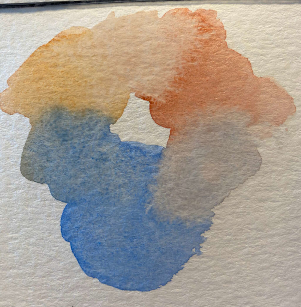 Triad colours painted on a scrap piece of paper, showing how they blend
